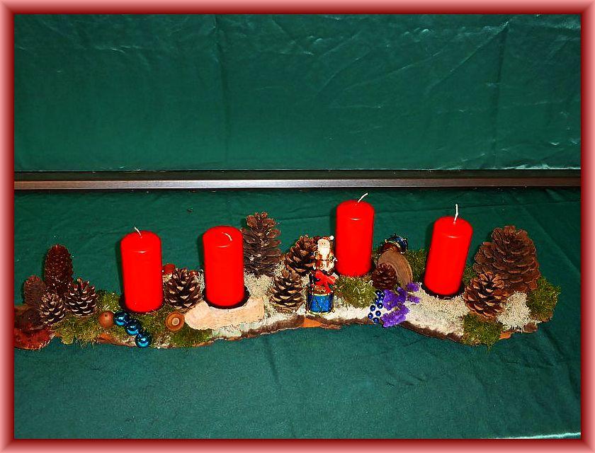 11. Etwa 80 cm langes, 12 cm tiefes 4er Gesteck mit roten Stumpenkerzen auf Baumrinde mit Moos, Rentierflechten, Zapfen, Flachem Lackporling, Rotrandigem Baumschwamm sowie dezenter Weihnachtsdekoration zu 15,00 €.