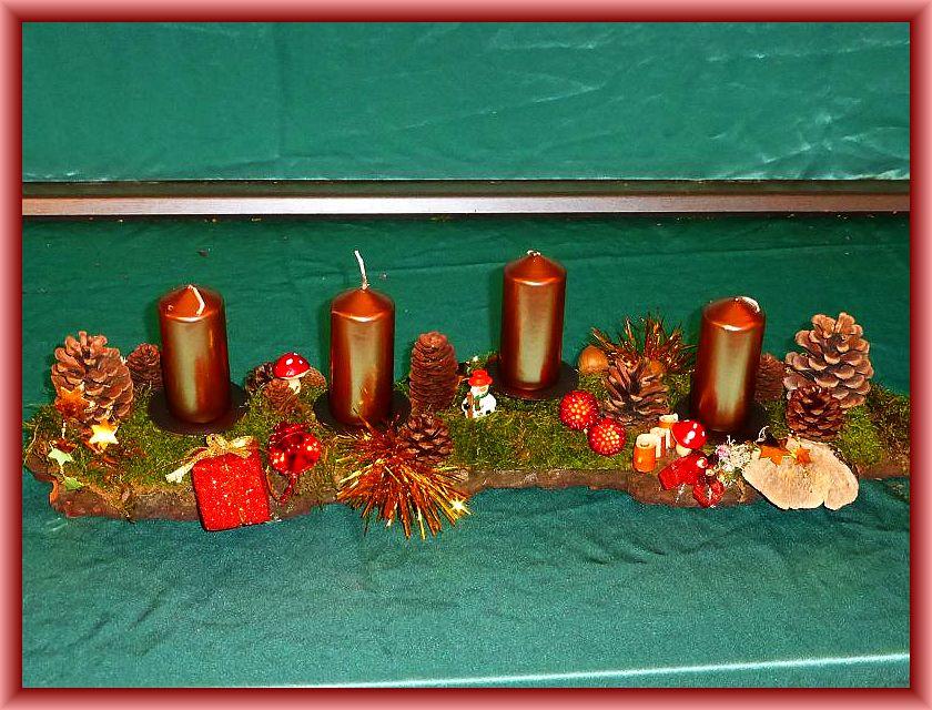 15. Etwa 60 cm langes, bis 12 cm tiefes 4er Gesteck auf Baumrinde mit bronzefarbenen Stumpenkerzen, Moos, Zapfen und Weihnachtsdekoration zu 15,00 €.
