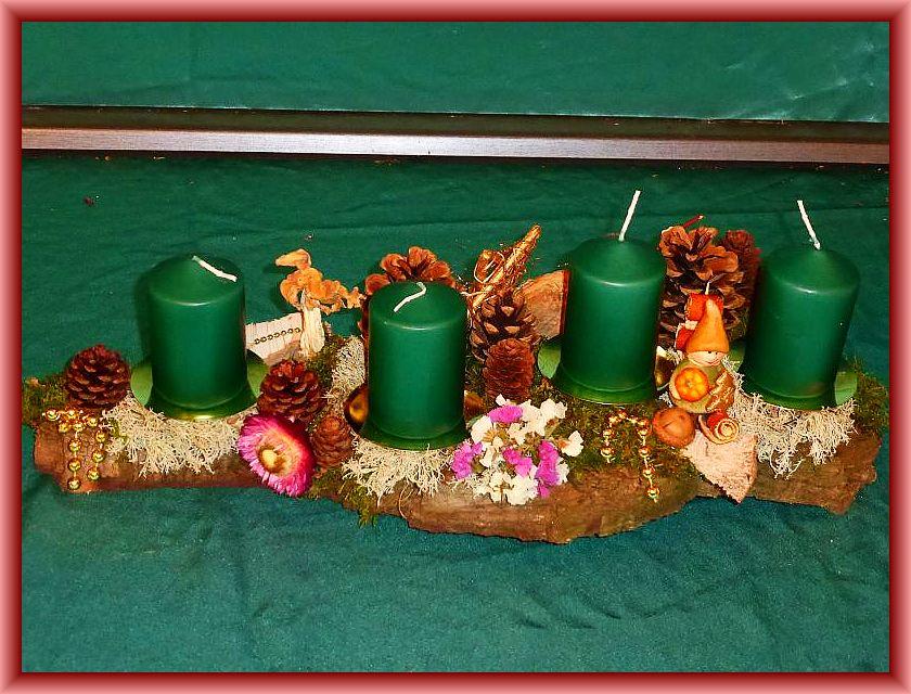 16. Ovales 4er Gesteck auf Baumrinde mit dunkelgrünen Stumpenkerzen, Moos, Rentierflechte, Trockenblumen, Zapfen, Eichenwirrling, Herbstlorchel,  und dezenter Weihnachtsdekoration zu 12,50 €.