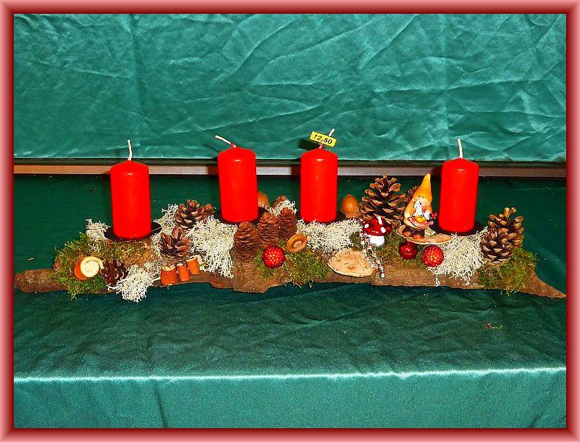 17. - Etwa 60 cm langes, bis 12 cm tiefes 4er Gesteck mit roten Stumpenkerzen, Moos, Rentierflechte, Zapfen, Flacher Lackporling, Striegeliger Tramete und Weihnachtsdekoration zu 12,50 €.