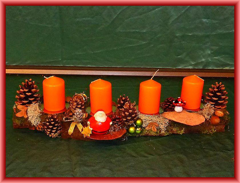 18. Etwa 60 cm langes, bis 15 cm tiefes 4er Gesteck mit terracottafarbenen Stumpenkerzen auf Baumrinde mit Moos, Rentierflechte, Zapfen,  Rötender Tramete und Weihnachtsdekoration zu 12,50 €.