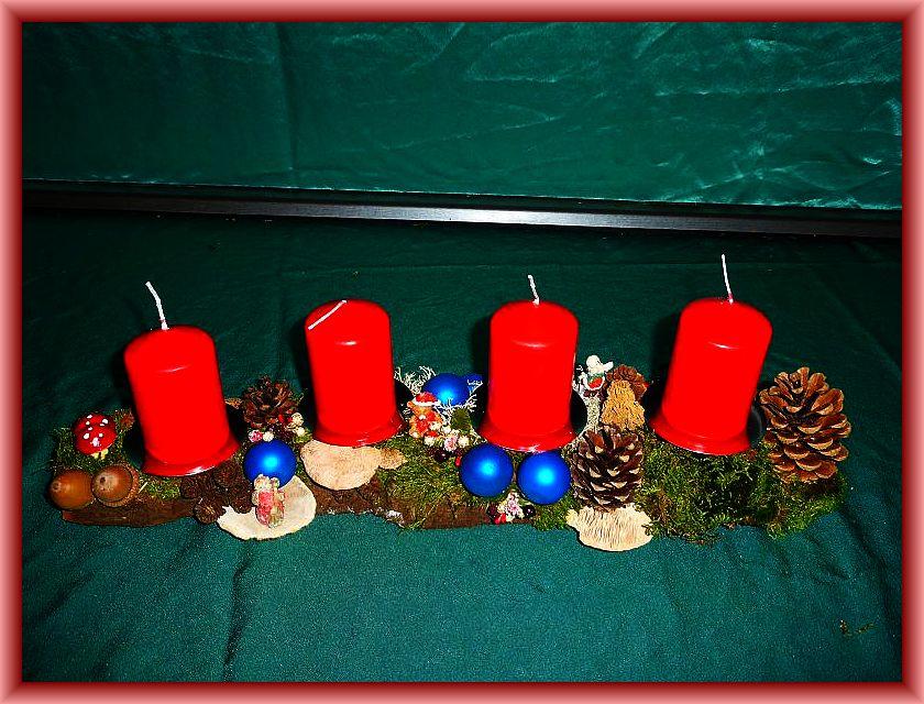 19. Etwa 50 cm langes, bis 12 cm tiefes 4er Gesteck auf Baumrinde mit roten Stumpenkerzen, Moos, Zapfen, Eichenwirrling, Rötender Tramete, Striegeliger Tramete und Weihnachtsdekoration zu 12,50 €.
