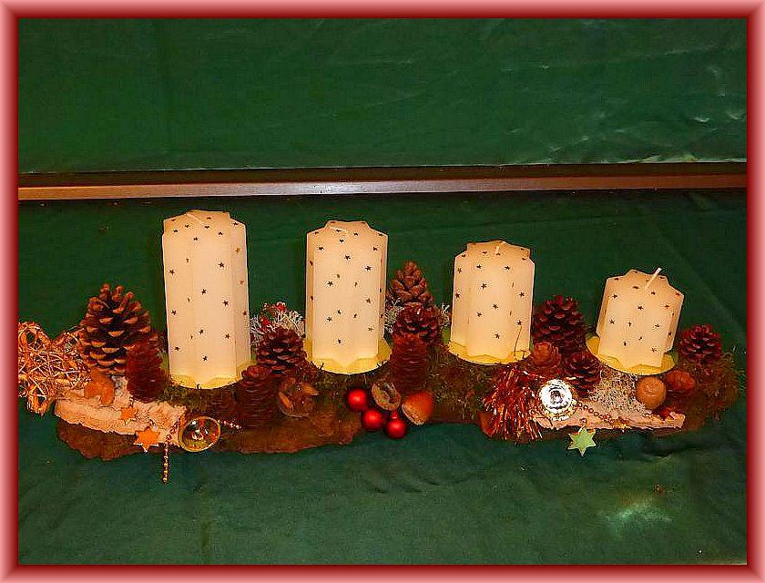 20. Etwa 60 cm langes, bis 15 cm tiefes 4er Gesteck auf Baumrinde mit weißen Sternenkerzen mit Moos, Zapfen, Eichenwirrling und Weihnachtsdekoration zu 15,00 €.