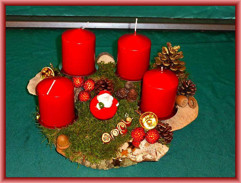21. Rundliches 4er Gesteck mit ca. 30 cm Durchmesser mit roten Stumpenkerzen auf Holzscheibe mit Moos, Eichenwirrling, Striegeliger Tramete, Zapfen und Weihnachstdekoration zu 15,00 €.