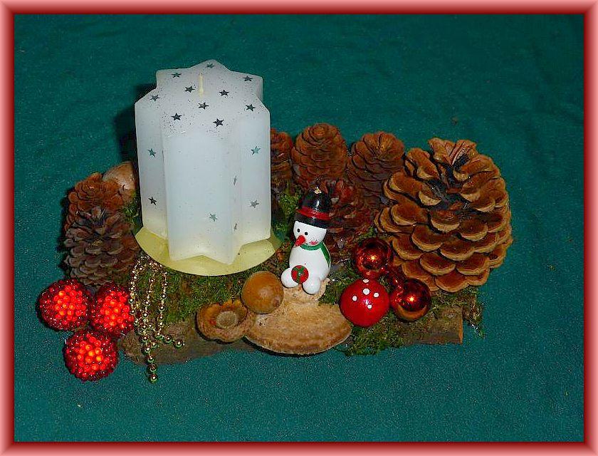 22. Etwa 18 cm langes und ca. 10 cm tiefes 1er Gesteck mit weißer Sternkerze, Moos, Eichenwirrling, Zapfen und Weihnachtsdekoration zu 5,00 € - Verkauft.