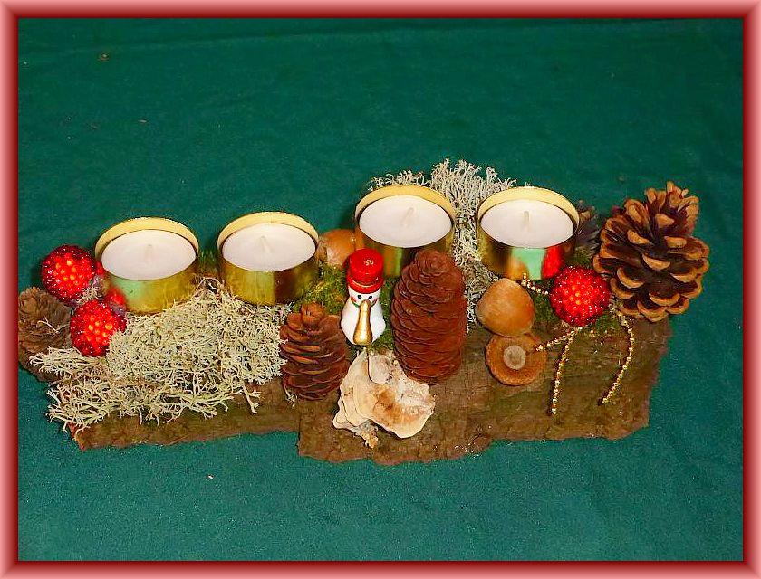23. Etwa 25 cm langes und 8 cm tiefes 4er Gesteck mit Teelichtern auf Baumrinde mit Moos, Rentierflechte, Zapfen, Schmetterlingstramete und Weihnachtsdekoration zu 6,00 €.