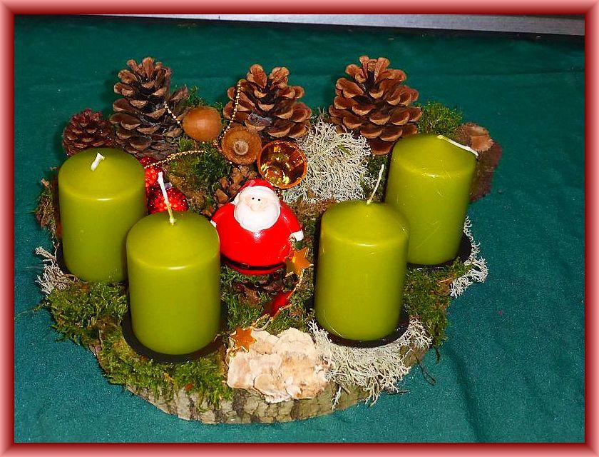 24, Rundliches 4er Gesteck auf Holzscheibe, etwa 25 cm im Durchmesser mit pistaziengrünen Stumpenkerzen, Moos, Rentierflechte, Zapfen, Schmetterlings - Tramete und Weihnachtsdekoration zu 12,50 €.