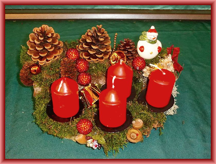 25. Rundliches 4er Gesteck mit etwa 25 cm im Durchmesser mit roten Stumpenkerzen, Moos, Rentierflechte, Zapfen, Schmetterlingstramete und Weihnachtsdekoration zu 12,50 €.