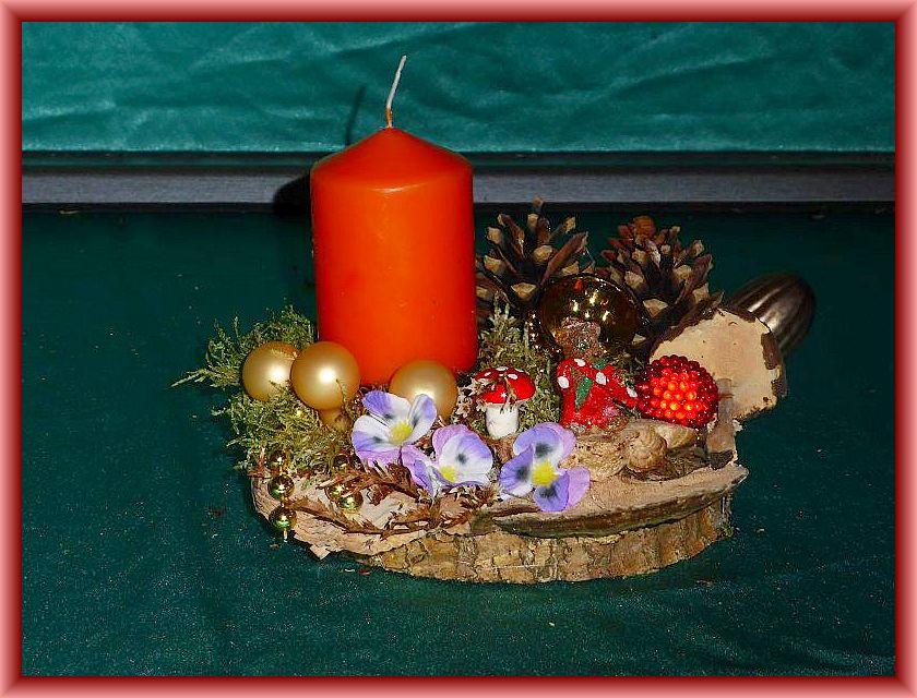 28. Rundliches 1er Gesteck mit orangeroter Stumpenkerze auf Baumscheibe, ca. 15 cm im Durchmesser mit Rötender Tramete, Winterporling, Zapfen, Moos und Weinhnachtesdekoration zu 5,00 €.
