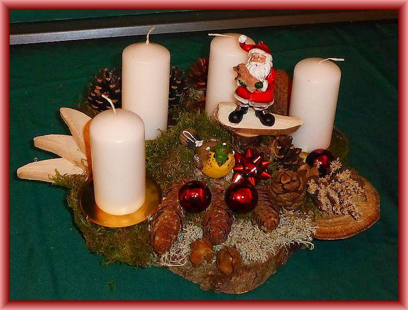 29. Rundliches 4er Gesteck auf Holzscheibe mit weißen Stumpenkerzen, Birkenporling, Rötender Tramete, Echtem Zunderschwamm, Moos, Rentierflechte und Weihnachtsdekoration zu 15,00 €.