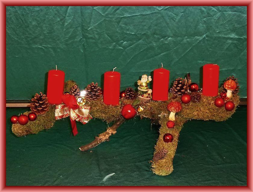 Etwa 70 cm langes, bis 30 cm tiefes 4er Gesteck mit roten Stumpenkerzen auf Astgabel mit Moos, Zapfen, Eichen - Wirrling und Weihnachtsdekoration zu 15,00 €.