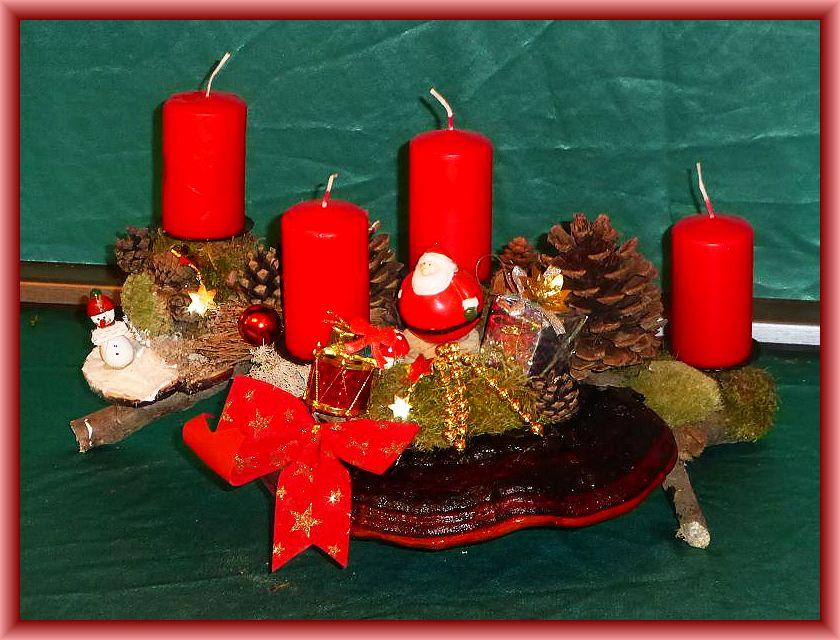32. Etwa 40 cm langes und bis 25 cm tiefes 4er Gesteck mit roten Stumpenkerzen auf Astgabel mit Rotrandigem Baumschwamm, Moos, Rentierflechte, Kiefernzapfen und Weihnachtsdekoration zu 15,00 €.
