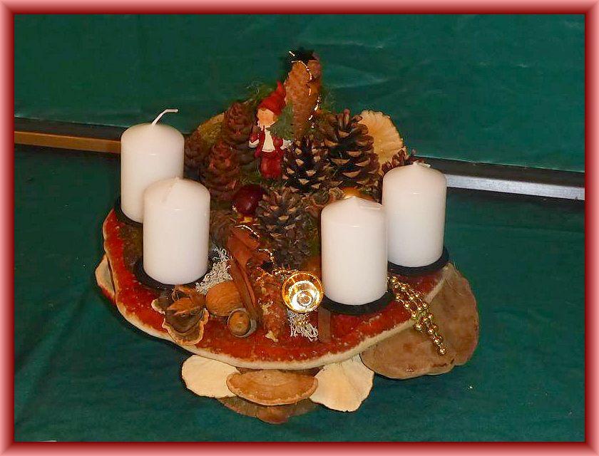 33. Kompaktes, rundliches 4er Gesteck auf Holzscheiben und Rotrandigem Baumschwamm, Echtem Zunderschwamm mit Schmetterlingstramete, Moos, Rentierflechte und weiteren Naturmaterislien sowie künstler Weihnachtsdekoration zu 20,00 €.