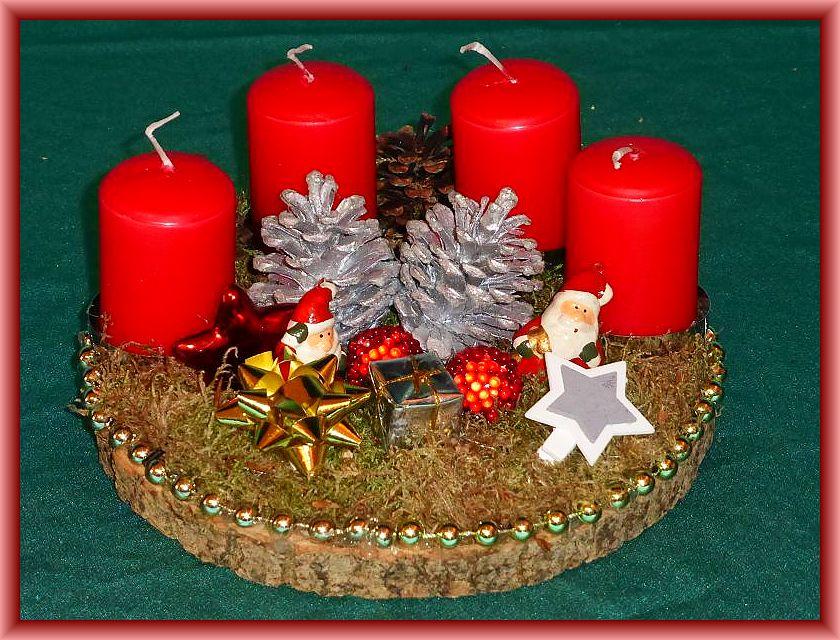 35. Rundes 4er Gesteck auf Baumscheibe, ca. 20 cm im Durchmesser, mit Moos, künstlicher Weihnachtsdekoration und roten Stumpenkerzen zu 6,00 €.