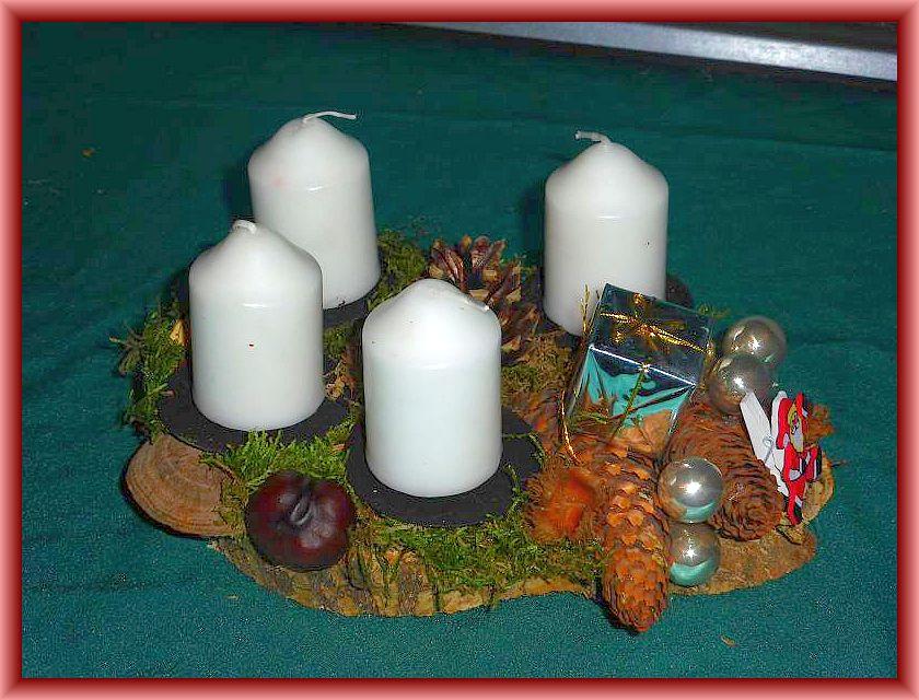 36. Rundliches 4er Gesteck auf Holzscheibe mit weißen Stumpenkerzen, Moos, Schmetterlingstrameten, Eichenwirrling und weiteren Naturmaterialien zu 5,00 € - Verkauft.