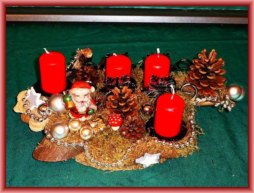 39. Gut 30 cm langes, bis 25 cm tiefes 4er Gesteck mit roten Stumpenkerzen auf Holzunterlage mit Schlitten, Striegeliger Tramete, Moos, Zapfen, Weihnachtsdekoration und silberner Perlenkette zu 10,00 €.
