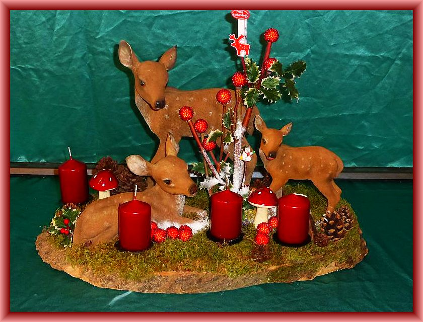 Großes, ovales 4er Gesteck mit Rehfanilie, ca. 60 cm im Durchmesser auf großer Holzscheibe mit Moos, Zapfen, Echtem Zunderschwamm und Weihnachtsdekoration zu 55,00 €.