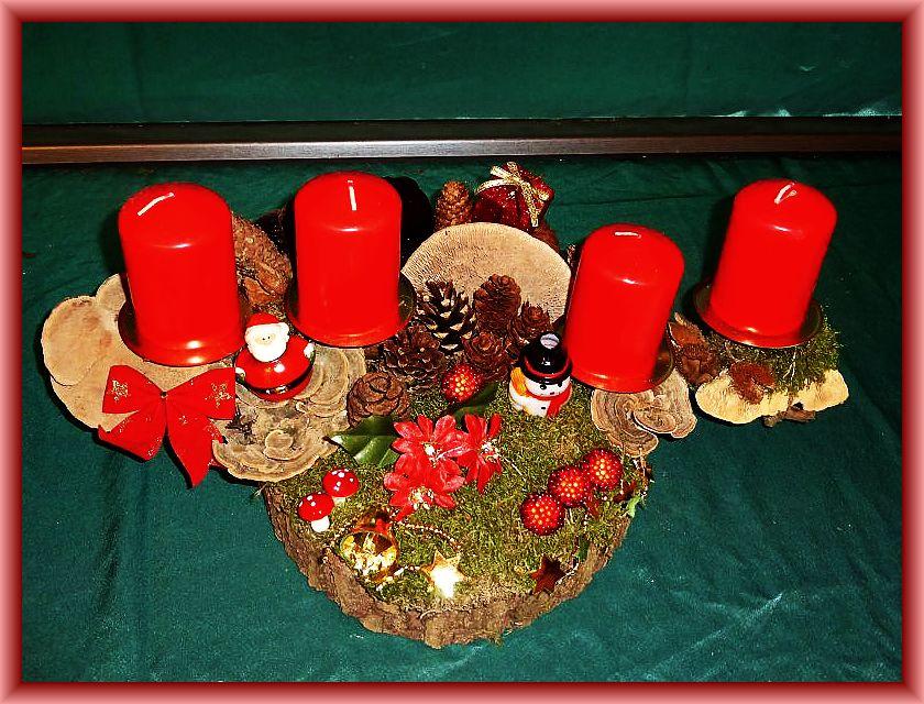 48. Ovales, großes 4er Gesteck mit roten Stumpenkerzen auf Baumscheibe und Ast mit Moos, Zapfen, Birkenbläätling, Schmetterlingstramete, Echtem Zunderschwamm, Rötender Tramete, Weihnachtsdekoration und roten Stumpenkerzen zu 20,00 €.