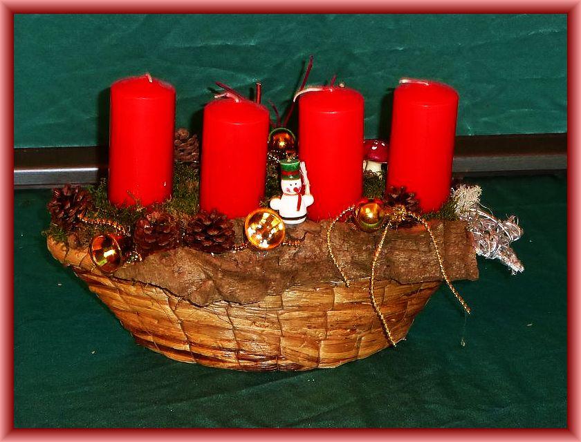 49. Ovales 4er Gesteck, 35 cm lang, 15 cm tief, mit roten Stumpenkerzen ohne Brennteller auf Flechtkorb und Baumrinde, Moos, Hartriegel, Zapfen und Weihnachtsdekoration zu 12,50 €.