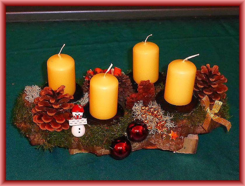 50. Ovales 4er Gesteck mit cremefarbenen Stumpenkerzen, ca. 30 cm lang, 12 cm tief auf Baumscheibe mit Moos, Zapfen, Rentierflechte, gerollten Orangenschalen und Weihnachtsdekoration zu 10,00 €.