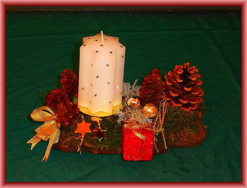 51. Kleines 1er Gesteck, gut 20 cm lang, bis 10 cm tief auf Holzrinde mit weißer Sternkerze, Moos, Zapfen und Weihnachtsdekoration zu 6,00 €.