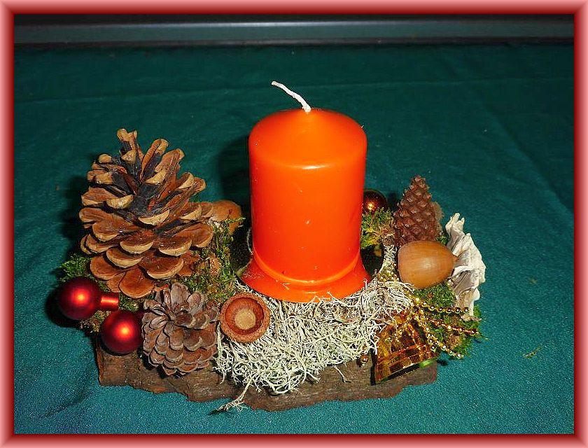 52. Kleines, knapp 20 cm langes, bis 8 cm tiefes 1er Gesteck mit orangefarbiger Stumpenkerze auf Baumrinde mit Moos, Rentierflechte, Angebrannten Rauchporlingen, Zapfen und Weihnachtsdekoration zu 5,00 €.