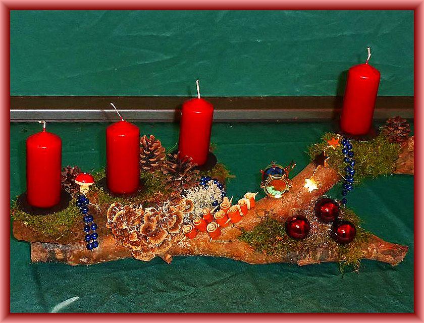 Gut 45 cm langes, bis 15 cm tiefes 4er Gesteck auf Astgabel mit burgundfarbenen Stumpenkerzen, Moos, Zapfen, Schmetterlingstrameten, gerollten Orangeschalen und Weihnachtsdekoration zu 12,50 €.