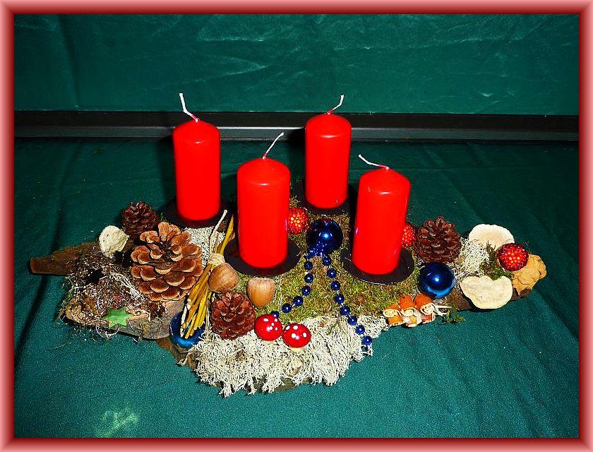 55. Gut 40 cm langes, bis 20 cm tiefes 4er Gesteck mit roten Stumpenkerzen auf Holz mit Moos, Rentierflechte, Herben Zwergknäuelingen, Striegeligen Trameten und etwas Weihnachtsdekoration zu 15,00 €.