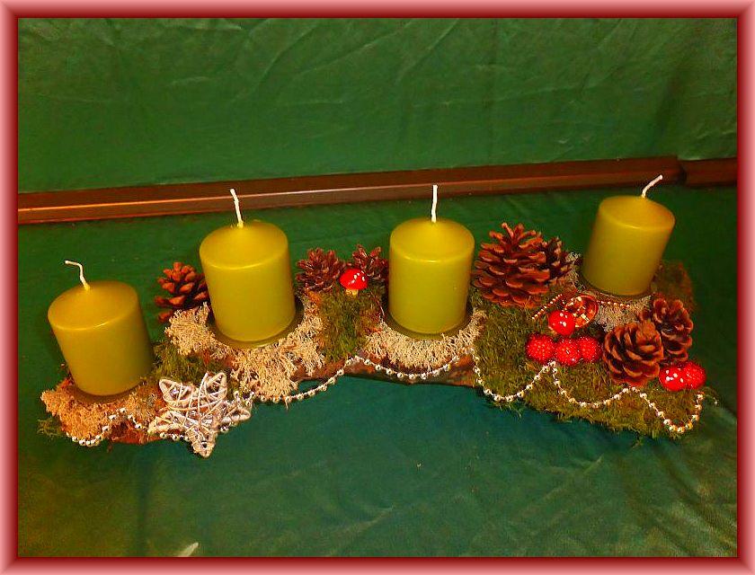 Gut 50 cm langes, bis 15 cm tiefes 4er Gesteck mit pistaziengrünen Stumpenkerzen auf Ast mit Moos, Rentierflechte, Weihnachtsdekoration und silberner Perlenkette zu 15,00 €.