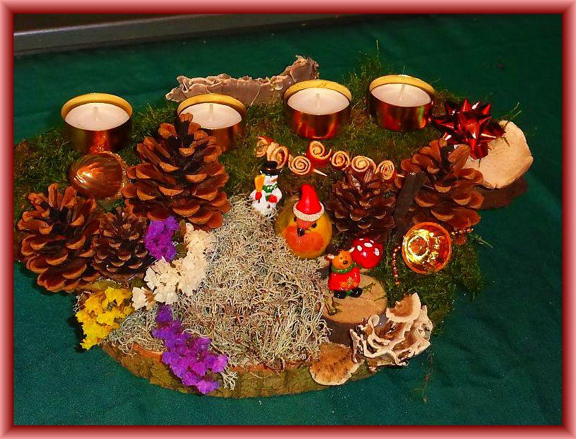 62. Ovales 4er Gesteck mit Teelichtern auf Baumscheibe und Holzrinde mit Moos, Rentierflechte, Schmettrerlingstramete, Angebrannten Rauchporlingen, Kiefernzapfen, gerollten Orasngenschalen und Weihnachtsdekoration zu 15,00 €.