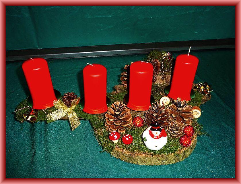 63. Etwa 45 cm langes, bis 25 cm tiefes 4er Gesteck mit roten Stumpenkerzen auf Baumscheibe und Baumrinde mit Moos, Kiefernzapfen, gerollten Orangenschalen und Weihnachtsdekoration zu 15,00 €.