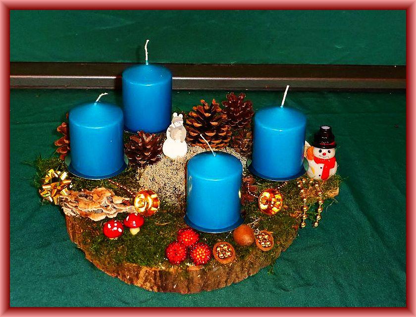 64. Rundlichovales 4er Gesteck, etwa 30 cm im Durchmesser mit petrolblauen Stumpenkerzen auf Baumscheibe mit Moos, Rentierflechte, Angebranten Rauchporlingen, Kiefernzapfen und Weihnachtsdekoration zu 20,00 €.