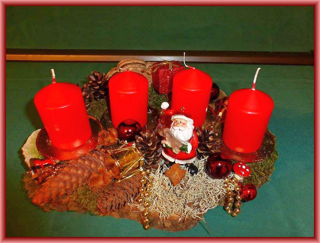 Ovales 4er Gesteck auf Baumscheibe mit roten Stumpenkerzen, Moos, Rentierflechte, Zapfen, Echtem Zunderschwamm, Rötender- und Striegeliger Tramete sowie Weihnachtsdekoration zu 15.00 €.