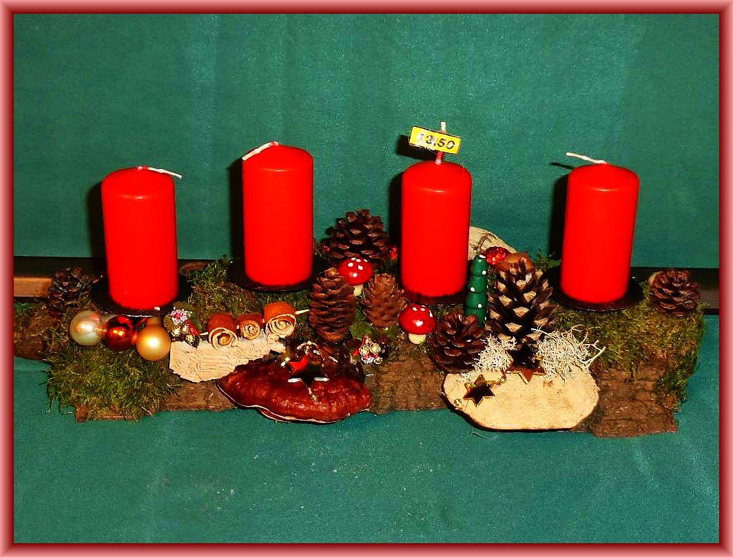 Etwa 40 cm langes, bis 15 cm tiefes 4er Gesteck auf Baumrinde mit roten Stumpenkerzen, Rötender Tramete, Rotrandigem Baumschwamm, Eichenwirrling, Moos, Zapfen und Weihnachtsdekoration zu 12.50 €.