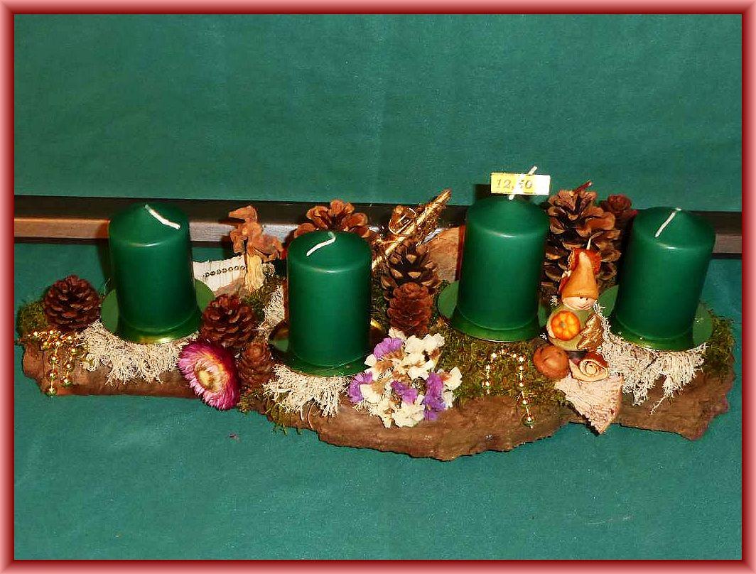 Gut 40 cm langes, 15 cm tiefes 4er Gesteck mit grünen Stumpenkerzen auf stabile Baumrinde mit Eichenwirrling, Moos, Rentierflechte, Trockenblumen und dezenter Weihnachtsdekoration zu 12.50 €.