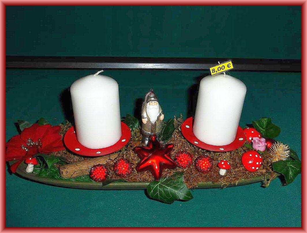 Längliches 2er - Gesteck mit weißen Stumpenkerzen auf Schale mit Moos und Weihnachtsdekoration zu 8.00 €.