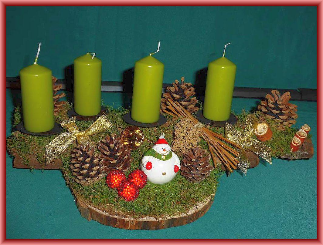 9. Gut 40 cm langes und bis 20 cm tiefes 4er Gesteck mit Stumpenkerzen in Pistazie auf Baumscheibe mit Moos sowie natürlicher und künstlicher Weihnachtsdekoration zu 12.50 €.