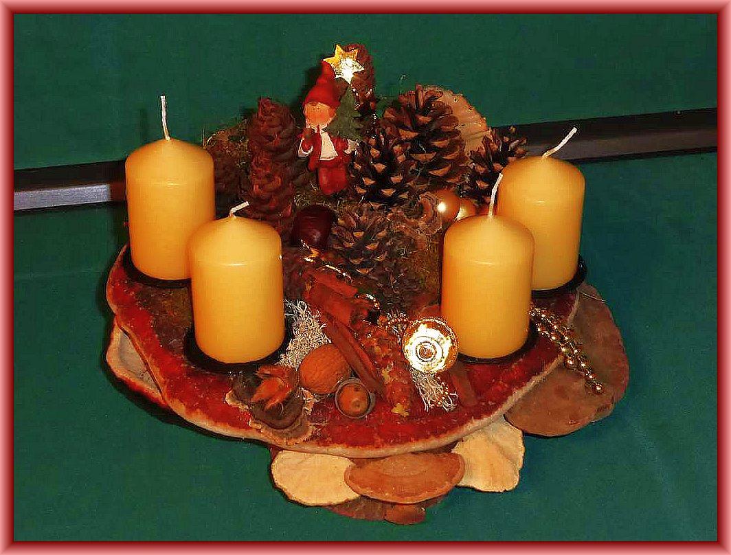 10. Rundliches 4er - Gesteck mit cremfarbenen Stumpenkerzen auf Baumscheibe und Pilzen. Rotrandige Baumschwämme, Echter Zunderschwamm, Striegelige Tramete, Eichen - Wirrling und weiterer Naturdekoration und zusätzlichem Weihnachtsschmuck zu 15.00 €.