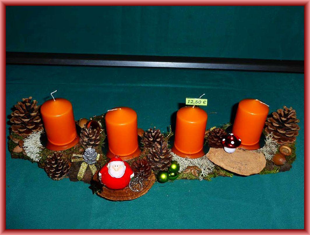 11. Etwa 50 cm langes, 12 cm tiefes 4er - Gesteck auf stabiler Baumrinde und orangefarbenen Stumpenkerzen. Mit Moos, Rentierflechte, Rötender Tramete, Kiefernzapfen und Weihnachtsdekoration für 12.50 €.