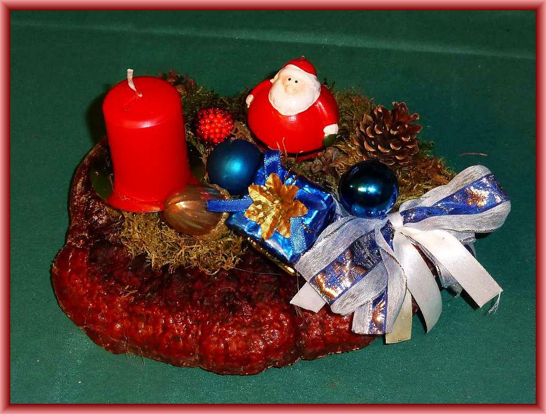 Ovales 1er - Gesteck, etwa 25 cm lang und 15 cm tief mit roter Stumpenkerze auf Rotrandigem Baumschwamm, mit Moos, Kiefernzapfen und Weihnachtsdekoration zu 5.00 €.