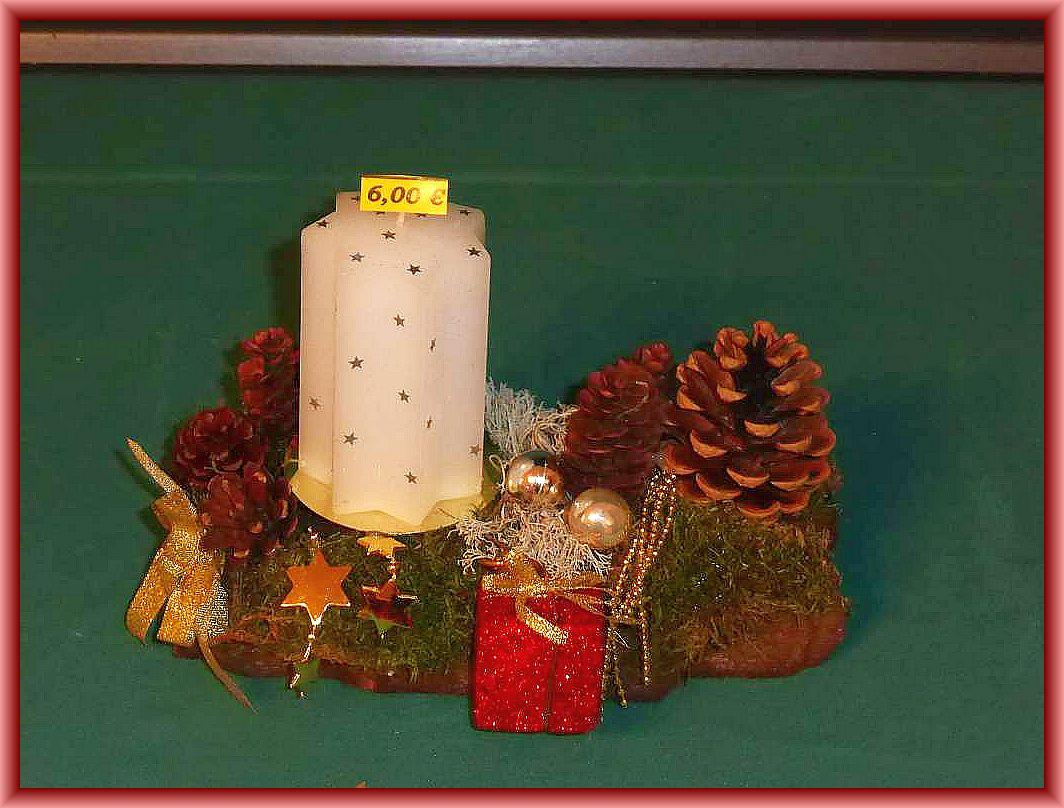 14. Kleines, etwa 20 cm langes, bis 10 cm tiefes 1er Gesteck mit weißer Sternkerze auf stabiler Baumrinde mit Moos, Zapfen, Rentierflechte und künstlicher Weihnachtsdekoration zu 6.00 €.