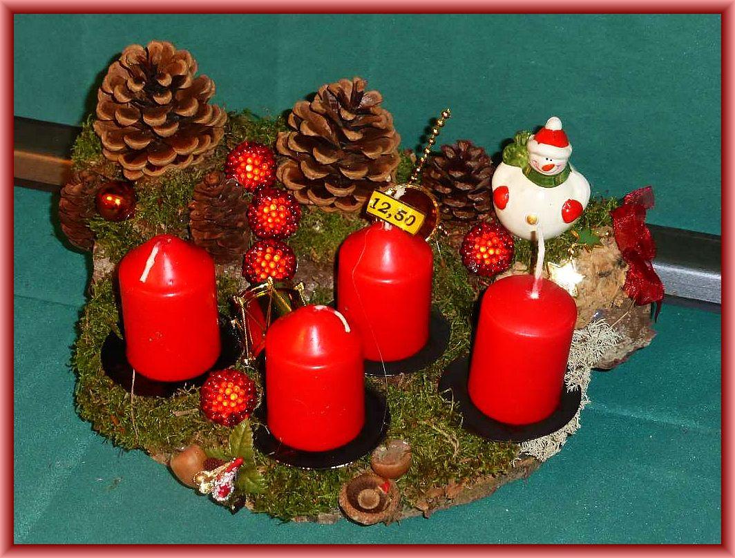 15. Rundliches, etwa 35 cm im Durchmesser betragendes 4er Gesteck mit roten Stumpenkerzen auf Baumscheibe mit Moos, Kiefernzapfen und Weihnachtsdekoration für 12.50 €.