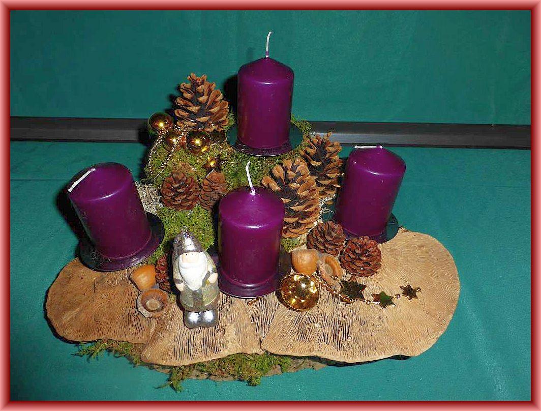 Recht großes, trapetzförmiges 4er Gesteck mit dunkelvioletten Stumpenkerzen auf Baumscheibe mit Eichenwirrlingen, Moos, Kiefernzapfen Weihnachtsdekoration. Durchmesser etwa 40 cm zu 20.00 €.
