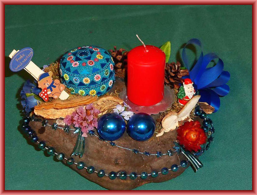 19. Rundliches 1er Gesteck auf Lackporling mit Striegeliger Tramete, roter Stumpenkerze, Moos und überwiegend in blau gehaltener Weihnachtsdekoration für 8.00 €.