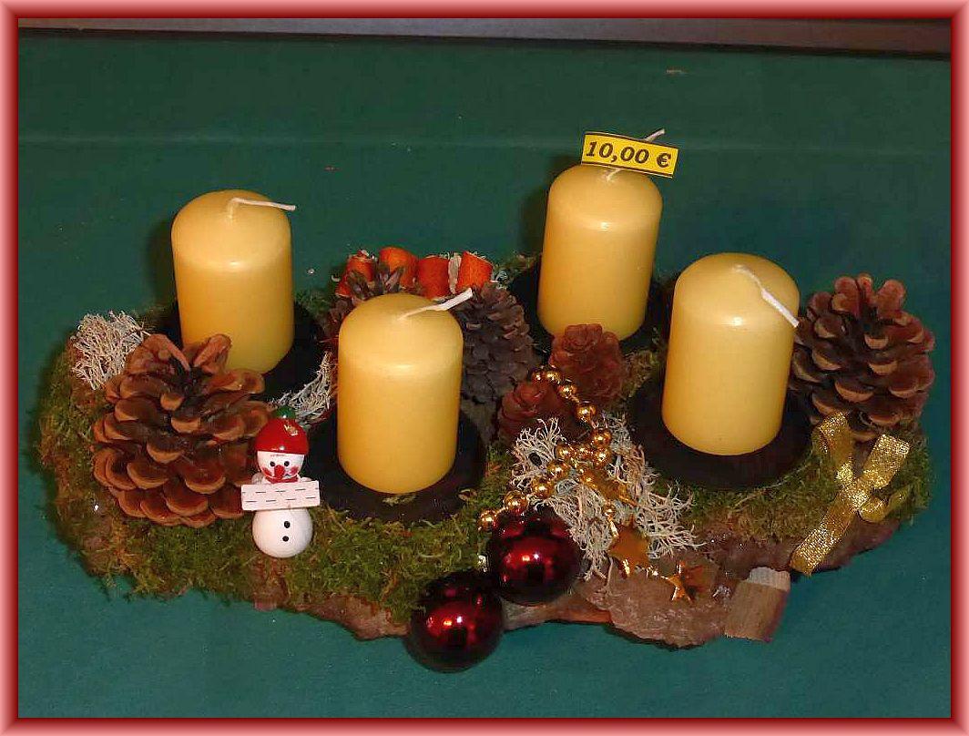 Längliches 4er Gesteck auf stabiler, etwa 25 cm langer, bis 10 cm tiefer Baumrinde mit cremefarbenen Stumpenkerzen, Moos, Rentierflechte, Zapfen und Weihnachtsdekoeration zu 10.00 €.