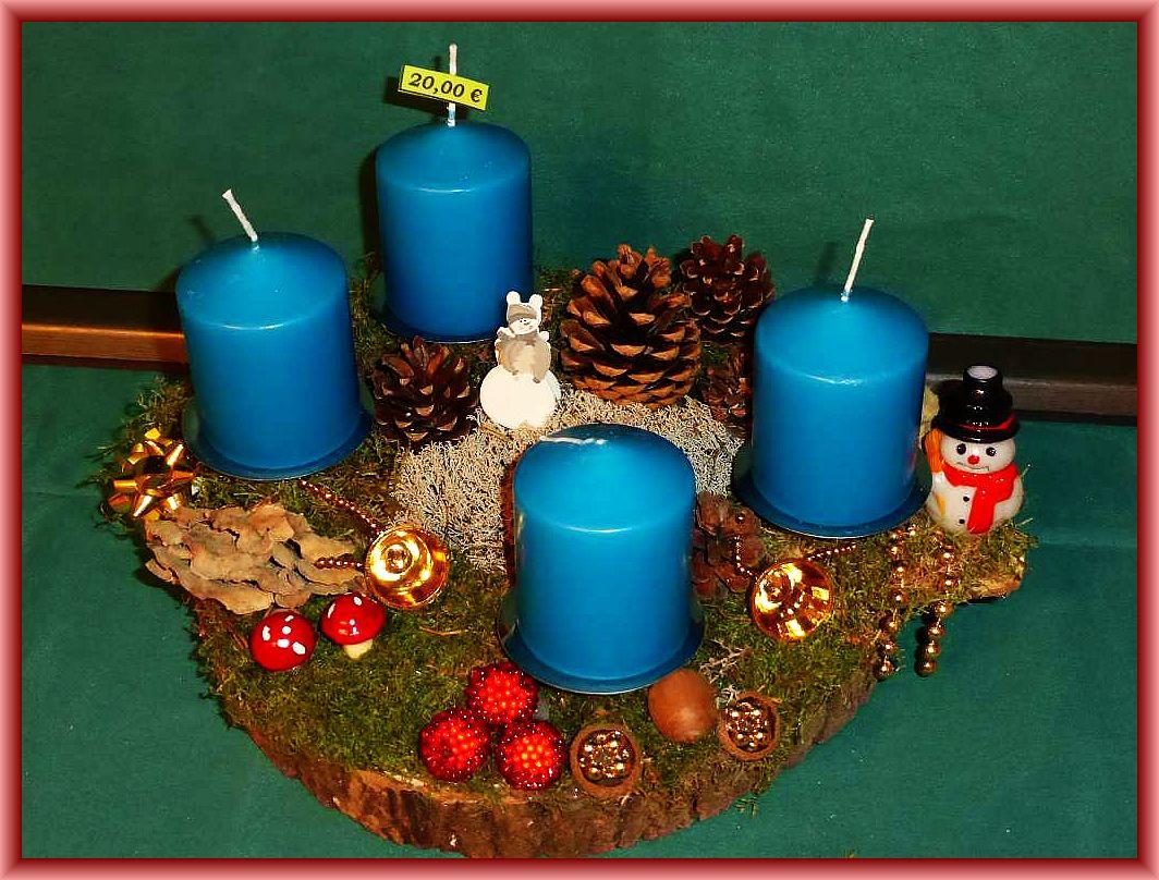Rundliches 4er Gesteck auf Baumscheibe mit ca. 30 cm Durchmesser, Moos, petrolblauen Stumpenkerzen, Angebrannten Rauchporlingen, Zapfen, Rentierflechte und Weihnachtsdekoration für 20.00 €.