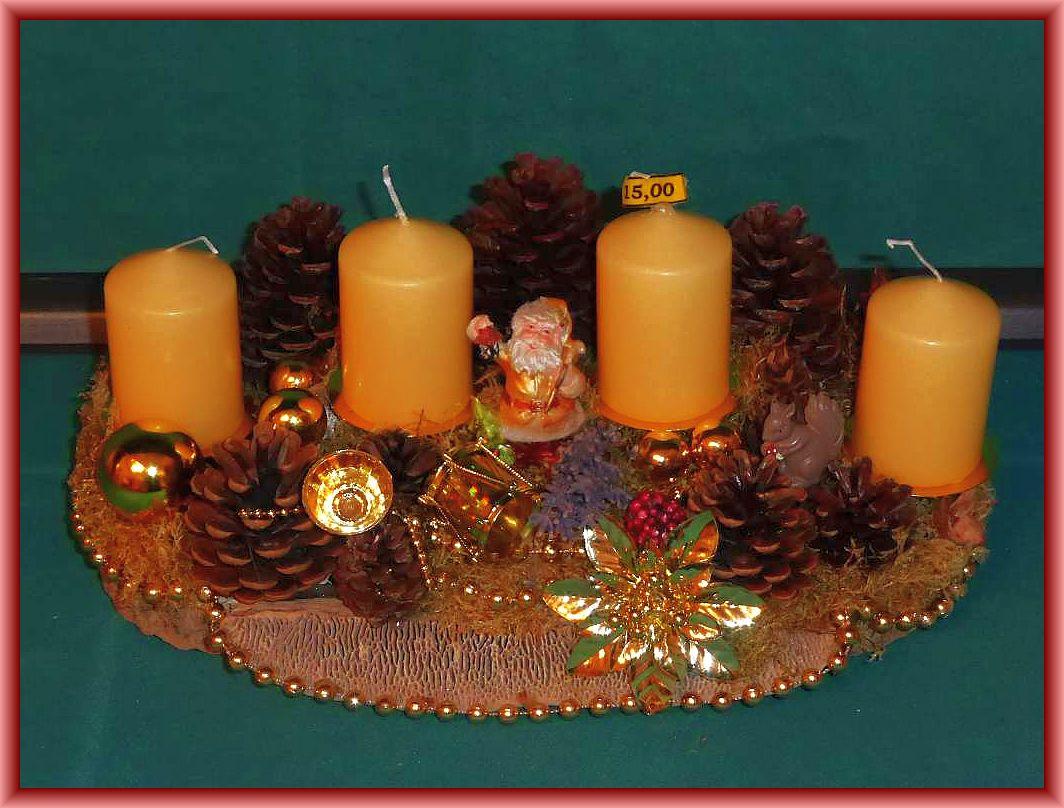 Ovales 4er Gesteck auf Baumscheibe und Eichenwirrling, mit cremefarbenen Stumpenkerzen, Moos, vielen Kiefernzapfen und in gold gehaltener Weihnachtsdekoration zu 15.00 €.