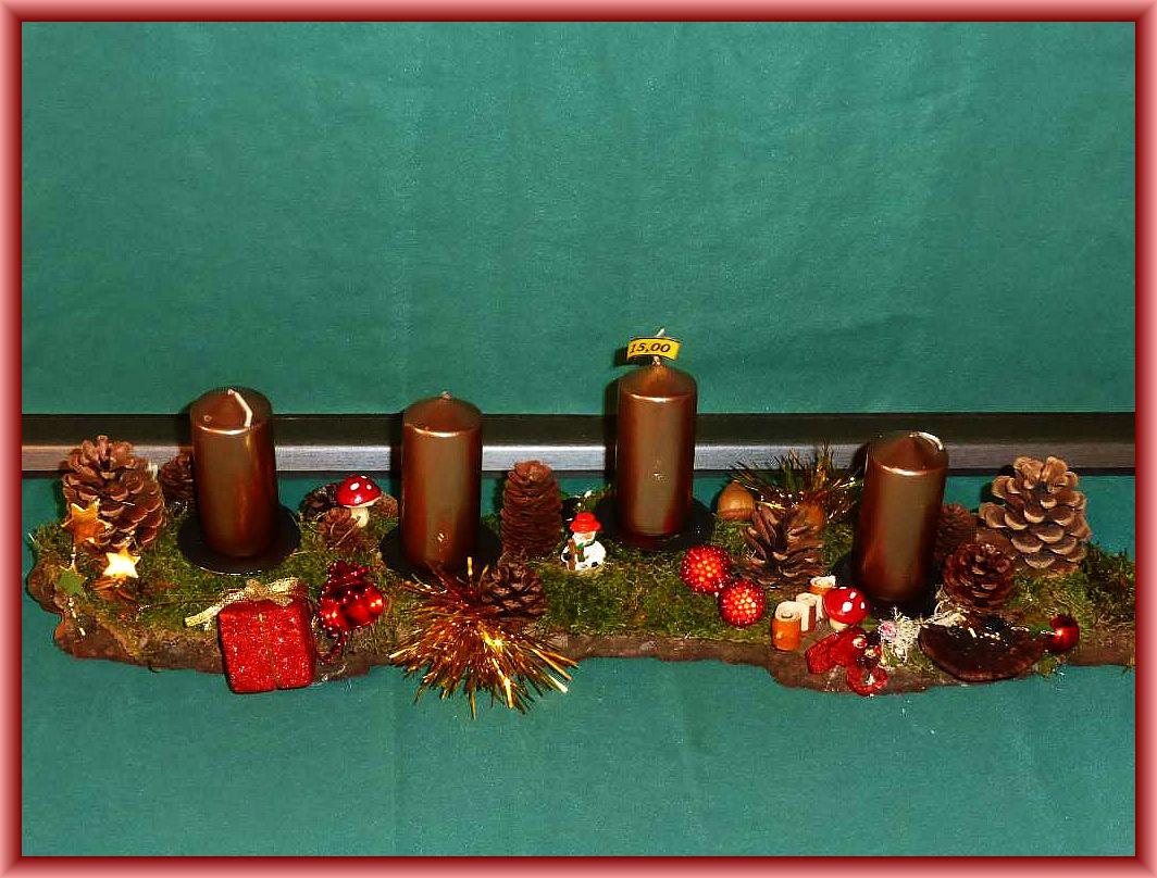 25. Etwa 60 cm langes, 10 cm tiefes 4er Gesteck mit bronzefarbenen Stumpenkerzen auf stabiler Baumrinde mit Moos, Rötender Tramete, Kiefernzapfen, Eicheln und Weihnachtsdekoration zu 15.00 €.