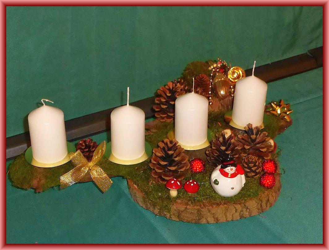 27. Gut 40 cm langes und bis 30 cm tiefes 4er Gesteck mit weißen Stumpenkerzen auf Baumscheibe und stabiler Baumrinde mit Moos, Kiefernzapfen und Weihnachtsdekoration zu 15.00 €.