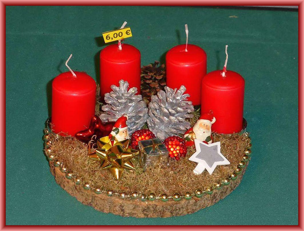 28. Rundes 4er Gesteck auf Baumscheibe, etwa 20 cm im Durchmesser mit Moos, Zapfen, silberner Perlenkette und Weihnachtsdekoration für 6.00 €.